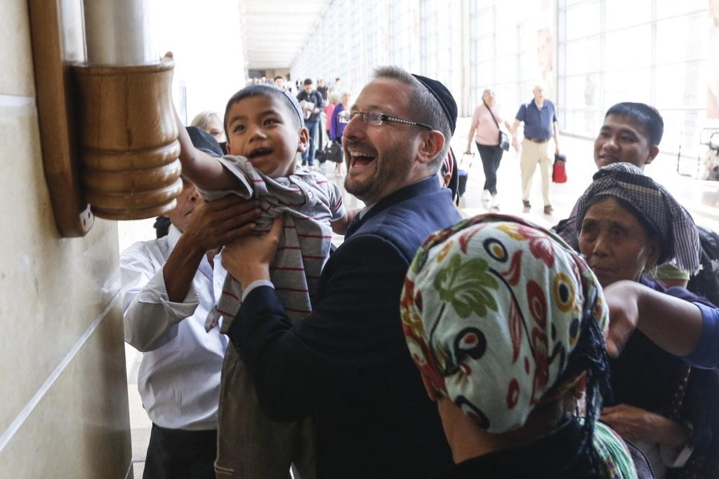 Child of the Bnei Menashe being uplifted by MK Dov Lipman to kiss the giant mezzuzah at Ben Gurion airport. (Photo: Shavei)