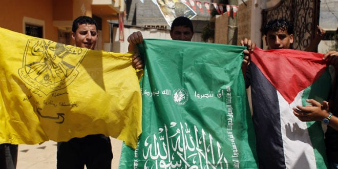 Palestinian protesters wave the flags of Palestinian political movements, Fatah (yellow) and Hamas (green) as they chant slogans in support of the national reconciliation and the announcement of the formation of a national unity government between the two factions, in Khan Yunis, in the southern Gaza Strip, on May 29, 2014. Palestinian premier Rami Hamdallah is to head the consensus government to be formed under a deal with Hamas to end seven years of rival administrations in the West Bank and Gaza, an official said. (Photo: Abed Rahim Khatib/ Flash90)
