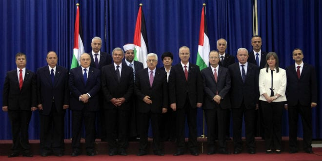 Palestinian unity government members including President Mahmoud Abbas (C), and Prime Minister Rami Hamdallah (5R), pose for a photo during during the swearing in ceremony of the government at the Palestinian Authority's headquarters in the West Bank town of Ramallah, on June 02, 2014. The government of national unity headed by Prime Minister Rami Hamdallah was sworn in by President Mahmoud Abbas and for the first time in seven years, the Palestinians have one government in charge of both the West Bank and the Gaza Strip. (Photo: Issam RImawi/FLASH90)