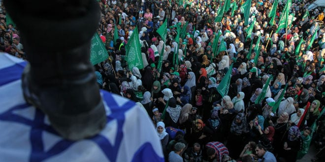 A terrorist of the Ezzedeen Al-Qassam Brigades stands over an Israeli flag, in front of Hamas supporters at a rally in Gaza City, Wednesday, Aug. 27, 2014. (Photo: Emad Nassar/Flash90)