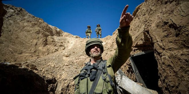 IDF soldiers seen standing next to the entrance of a Hamas terror tunnel where motorcycles and weapons were uncovered. (Photo: IDF)