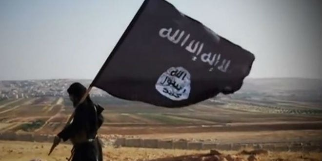 An ISIS insurgent seek walking with the groups flag.