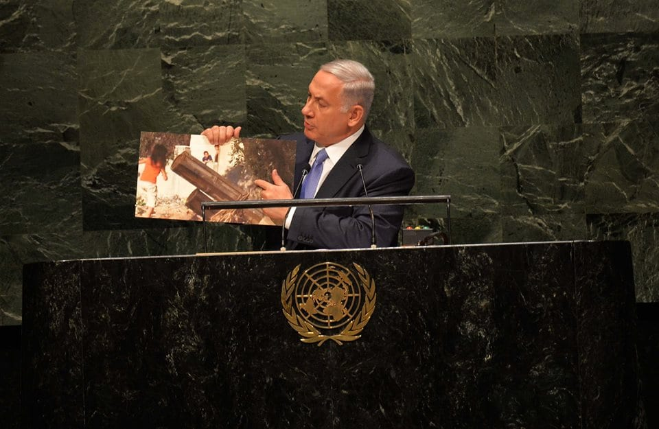 Netanyahu holding up an image taken by France's 24 News showing Hamas rocket launchers surrounded by children being used as human shields. (Photo: GPO)