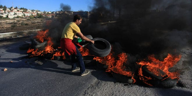 A Palestinian youth from the Jalazoun refugee camp throws burning tyres to block the road as he clash with Israeli soldiers, on the road at the entrance of the city of Beit El near Ramallah, following a march by Palestinian demonstrators against Israeli restrictions on the Al-Aqsa mosque. October 24, 2014. (Photo: STR/ Flash90)