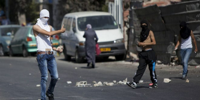 Palestinian youths hurl stones at Israeli police during clashes after Friday prayers in the East Jerusalem neighbourhood of Wadi al-Joz, October 17, 2014. Israeli police declared an age limit on Friday for Palestinians wanting to enter the Old City, only allowing males above the age of 50 and all females to enter. (Photo: Yonatan Sindel/Flash90)