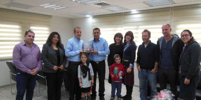 Rabbi Tuly Weisz (third from left) presenting Mayor of Sderot Alon Davidi (fourth from left) with over 8,000 signatures of people standing in solidarity with the city of Sderot, December 18, 2014. (Photo: Lea Speyer/ Breaking Israel News)