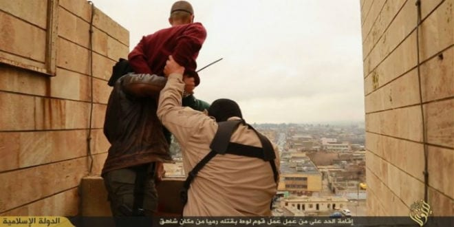 Masked ISIS terrorists are seen about to push a homosexual man off a building to his death as part of a public Koranic  execution. (Photo: Screenshot)