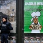 Gun-Toting God Graces Cover of Charlie Hebdo's Anniversary Issue Marking One Year Since Massacre