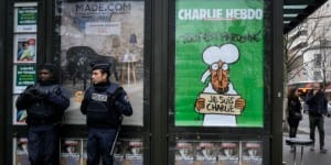 French police seen guarding outside a newspaper store advertising the latest cover of the satirical newspaper Charlie Hebdo, on January 15, 2015, in Paris, France, about a week after the newspaper offices were attacked by terrorists who killed several cartoonists and editors. (Photo: Serge Attal/Flash90)