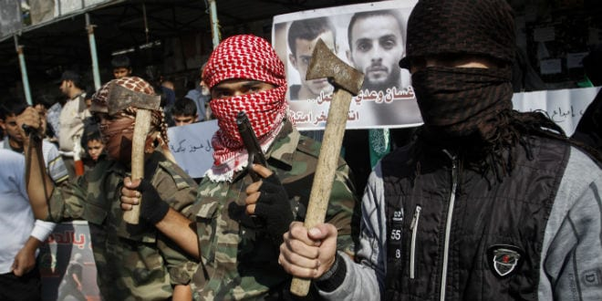 Masked Palestinians hold axes and a gun as they celebrate with others an attack on a Jerusalem synagogue, in Rafah in the southern Gaza Strip, on November 18, 2014. (Photo: Abed Rahim Khatib/Flash90)
