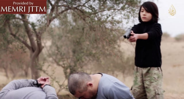 A young boy is seen shooting in the head two men accused of being spies. The boy is carrying out a death sentence on behalf of ISIS. (Photo: MEMRI)