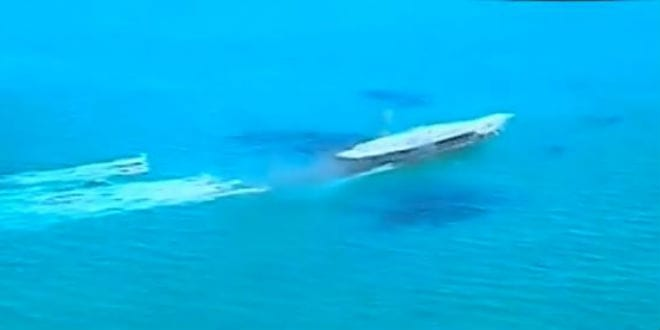 Iranian naval vessels approach a replica of a US aircraft carrier as part of a drill to destroy the vessel. (Photo: YouTube Screenshot)