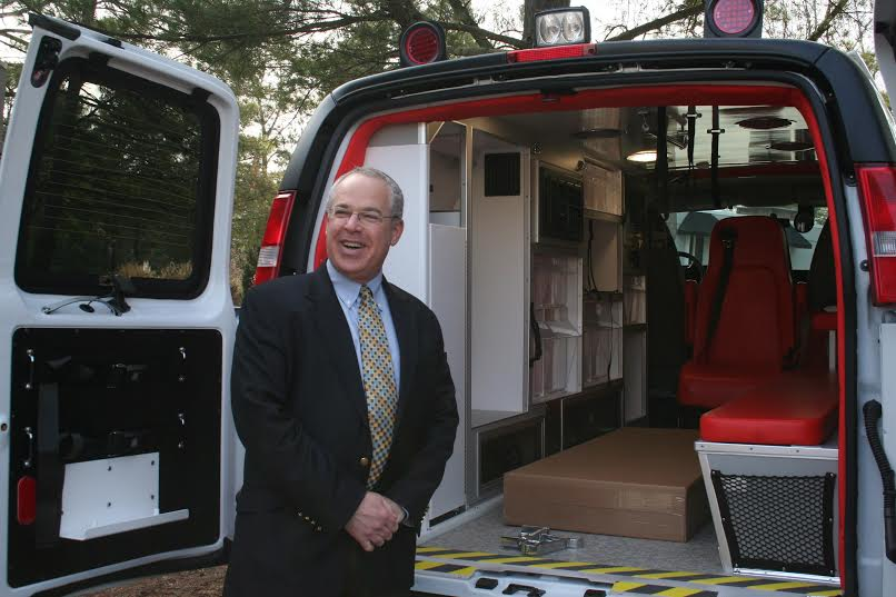 Jonathan Feldstein smiling and proud to be standing in front of the Bridges for Peace ambulance outside of Raleigh Angel Ministries. (Photo: Heart to Heart)