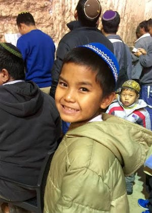 This young boy from Bnei Menashe puts on his blue kippah proudly to visit the Western Wall for the first time. (Photo: Israel Returns)
