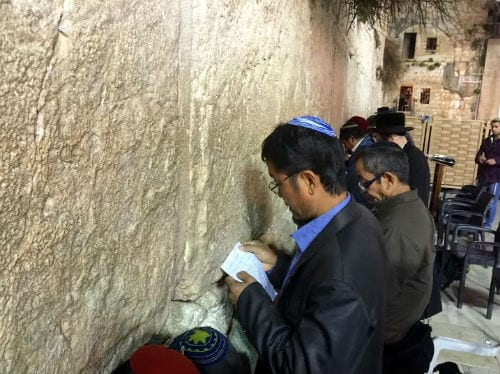 A man from Bnei Menashe reads a handwritten note as he stands face to face with the Western Wall. (Photo: Israel Returns)