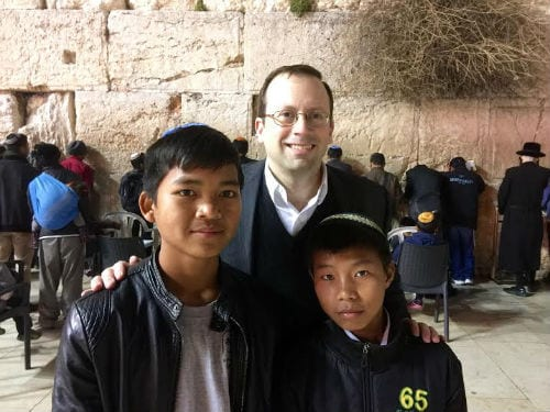 Michael Freund, founder and chairman of Israel Returns, in front of the Western Wall with two young men from the Bnei Menashe tribe. (Photo: Israel Returns)