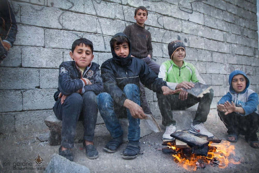 Assyrian Christian children who were displaced by the Islamic State terror group are pictured in Ankawa, Iraq, trying to keep warm during a snowstorm. (Photo: Jeff Gardner/ Picture Christians Project/ picturechristians.org)