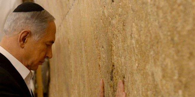 Israeli Prime Minister Benjamin Netanyahu prays at the Western Wall before his departure to the US. (Photo: GPO)