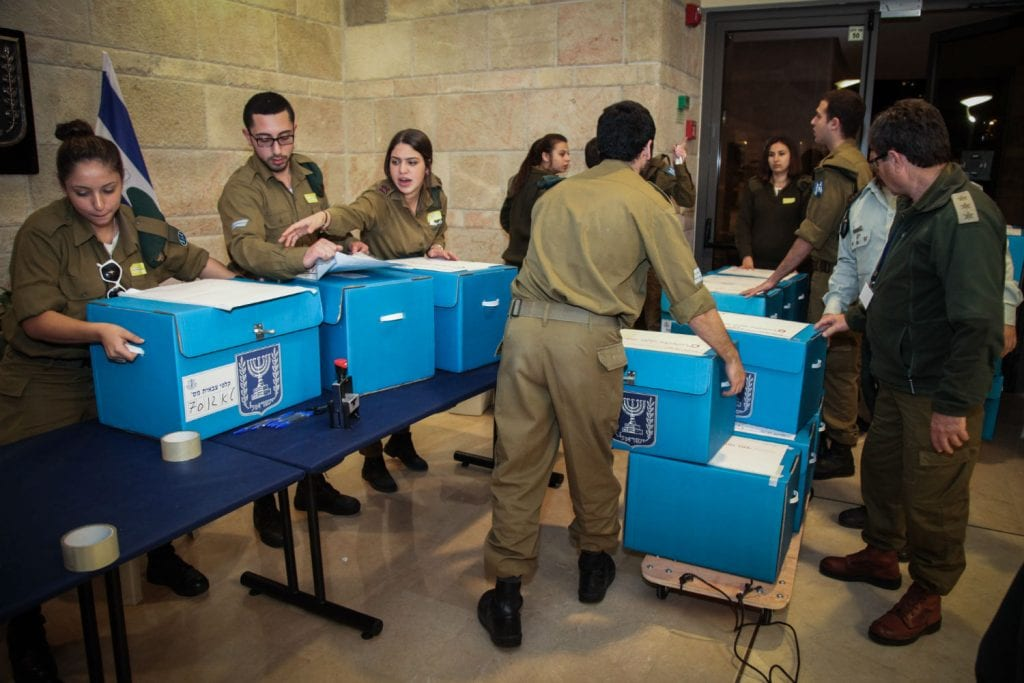 Israeli soldiers collect and transfer polling ballots from hospitals and army bases to be counted after the first exit polls were announced in the Israeli general elections for the 20th parliament on March 17, 2015. Photo by Isaac Harari/FLASH90