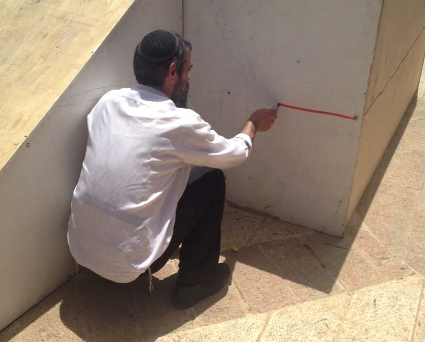 A kohen-priest prepares the altar. Note the ramp at the right. (Photo: Yisrael Rosenberg/ Breaking Israel News)