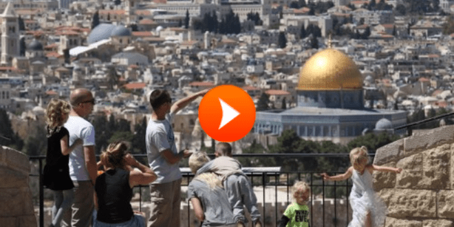 Tourists stand on a lookout point on Mount of Olives, overlooking Jerusalem Old City, with the Dome of the Rock