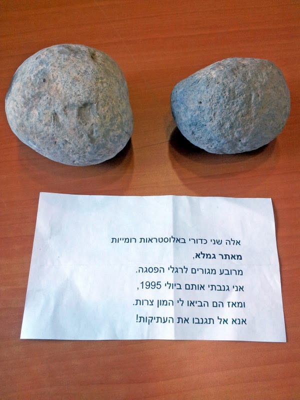 The trebuchet stones and the note accompanying them. (Photo: Dr. Dalia Manor/ Museum of Islamic and Near Eastern Cultures, Be'er Sheva)