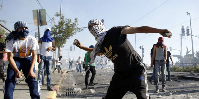 Illustrative: Masked Palestinians throw stones towards Israeli police (unseen) during clashes in the Shuafat neighborhood in East Jerusalem, on July 3, 2014. (Photo: Sliman Khader/FLASH90)