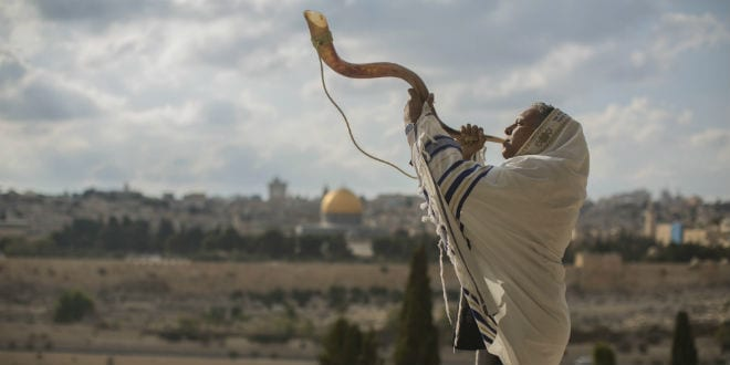 A man blows a  shofar. The Temple Mount in Jerusalem's Old City can be seen in the background. (Photo: Yonatan Sindel/Flash90