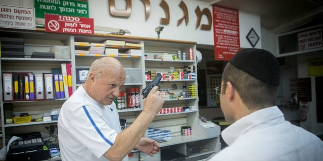 """A man buys a handgun at the """"Magnum 2525"""" store in Jerusalem, following the recent wave of terror attacks. (Photo: Miriam Alster/FLASH90)"""