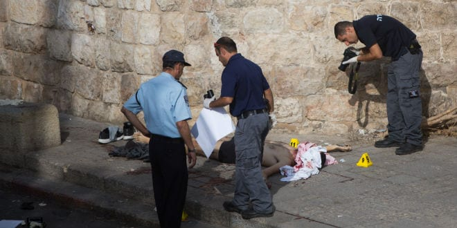 Israeli police standing near the body of a Palestinian terrorist at the scene where he attempted to stab a police officer took place near the Lion Gate in the Old City of Jerusalem on October 12, 2015. (Photo: Yonatan Sindel/Flash90)