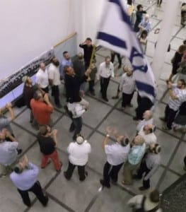 """Yehudah Glick waves the Israeli flag and dances with friends and supporters at """"Survival and Celebration"""" (Photo: Abra Forman/Breaking Israel News)"""