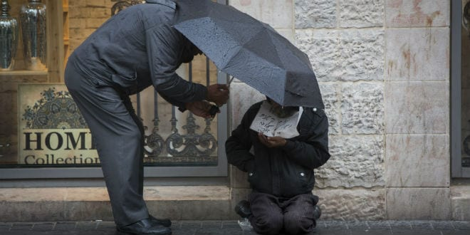A man gives money to a homeless person as he holds an umbrella to protect themselves from the rain on Jaffa street, downtown Jerusalem on November 3, 2014. (Photo: Yonatan Sindel/Flash90)