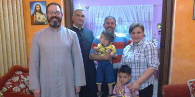 Father Luis Montes with an Iraqi Christian family. (Photo: Friends of Iraq/JNS)