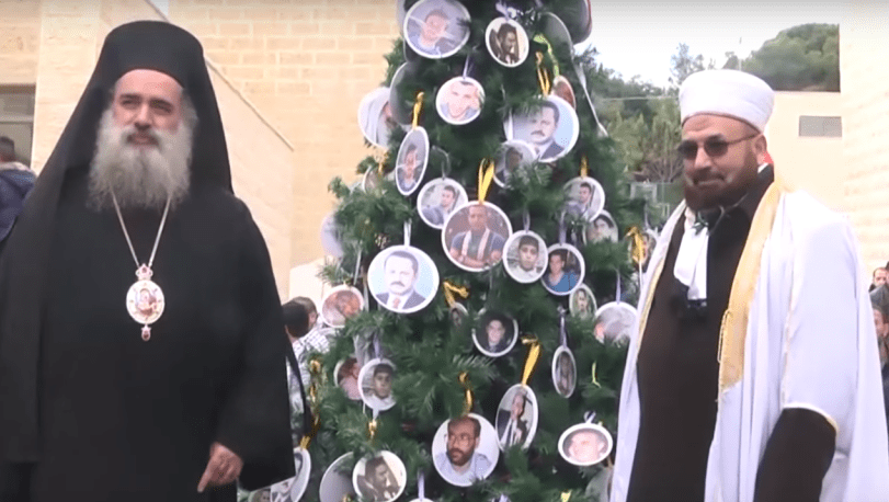 """Palestinian religious leaders stand next to a Christmas """"martyrs tree"""" at Al Quds University. (Photo: YouTube Screenshot)"""