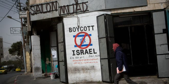 A Palestinian man walks by a graffiti sign calling to boycott Israel seen on a street in the city of Bethlehem on February 11, 2015. (Photo: Miriam Alster/Flash 90)