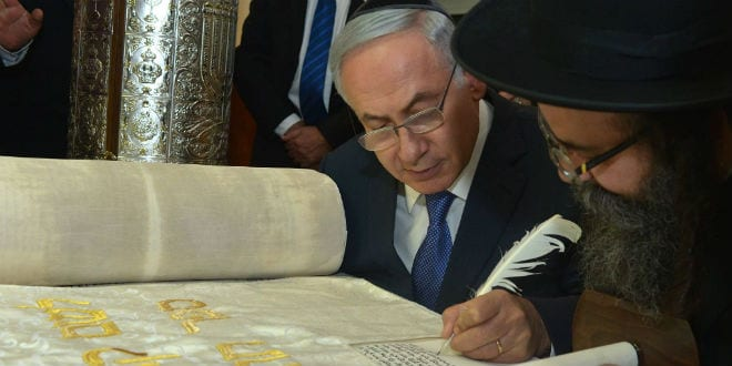Prime Minister Benjamin Netanyahu writes the final letters of a Torah scroll dedicated to Israel's fallen soldiers. (Photo: Kobi Gideon/GPO)