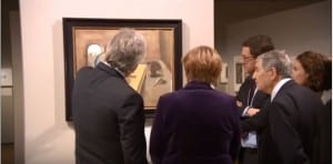 German Chancellor Angela Merkel (center) at an exhibit of Holocaust art on January 25, 2016. (Photo: YouTube)