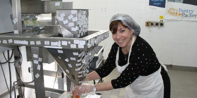 Tsivya Fox, Director of Client Relations at Breaking Israel News packages rice for underprivileged families at Colel Chabad's Pantry Packers in Jerusalem (Photo: Breaking Israel News)