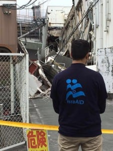 An IsraAID volunteer stands among the wreckage after a devastating earthquake shook southern Japan on Friday (Photo: Official IsraAID Facebook Page)