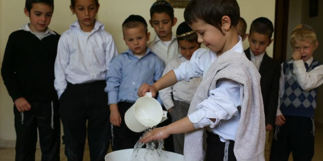 """The children wash their hands in preparation for eating vegetables known as Karpas (Photo: Here the boy lifts the Matzah and breaks it in two for the """"Urchatz"""" part which includes the washing of the hands. There are severaly stages: Kadeish, Urchatz, Karpas, Yachatz, Maggid, Rachtzah, Motzi, Maror, Koreich, Shulchan oreich, Tzafun, Bareich, Hallel, Nirtzah. Photo: Nati Shohat/Flash90)"""