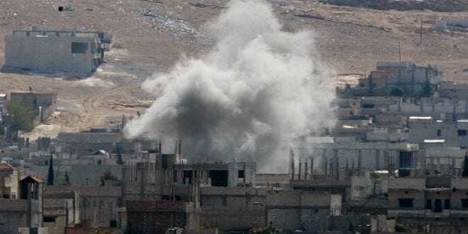 An explosion after an apparent US-led coalition airstrike on Kobane, Syria, as seen from the Turkish side of the border, near Suruc district. 17 October 2014, Turkey , Syria. (gungorkarakus / Shutterstock.com)