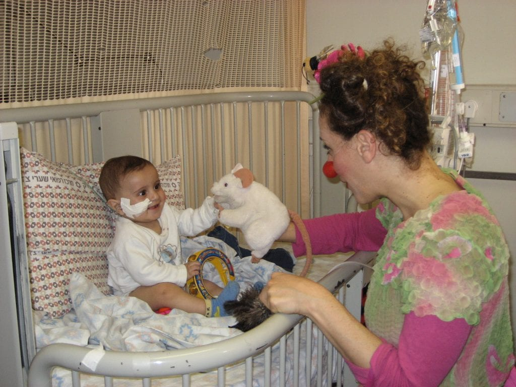A medical clown brings cheer to a baby in the hospital undergoing medical treatment. (Photo: Dream Doctors)