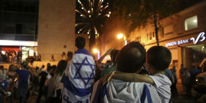 Israelis wrap themselves in the Israeli flag as they watch fireworks in central Jerusalem to celebrate Israel's 66th Independence Day, on May 05, 2014. (Photo: Hadas Parush/Flash 90)