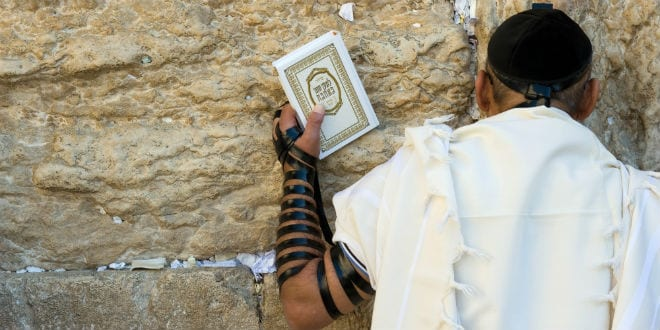 A man prays at the Western Wall (Kotel) wrapped in his prayer shawl and tefillin. (Robert Hoetink / Shutterstock.com)
