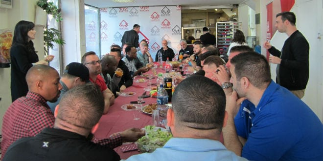 The young pastors of Eagles' Wings sit in the Jerusalem branch of Meir Panim and learn how their donation will help thousands of people. (Photo: Breaking Israel News)