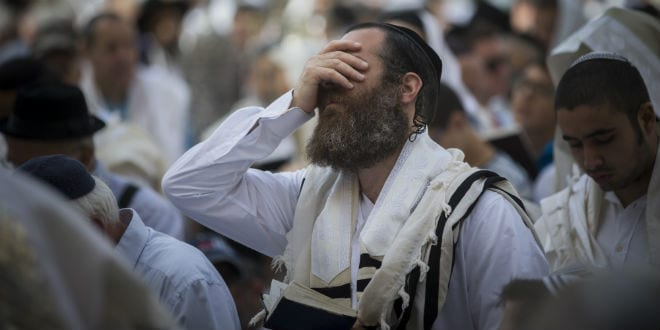 Jewish worshippers cover themselves with prayer shawls as they pray in front of the Western Wall, Judaism's holiest prayer site, in Jerusalem's Old City, during the Cohen Benediction priestly blessing at the Jewish holiday of Passover, April 25, 2016. (Yonatan Sindel/Flash90)