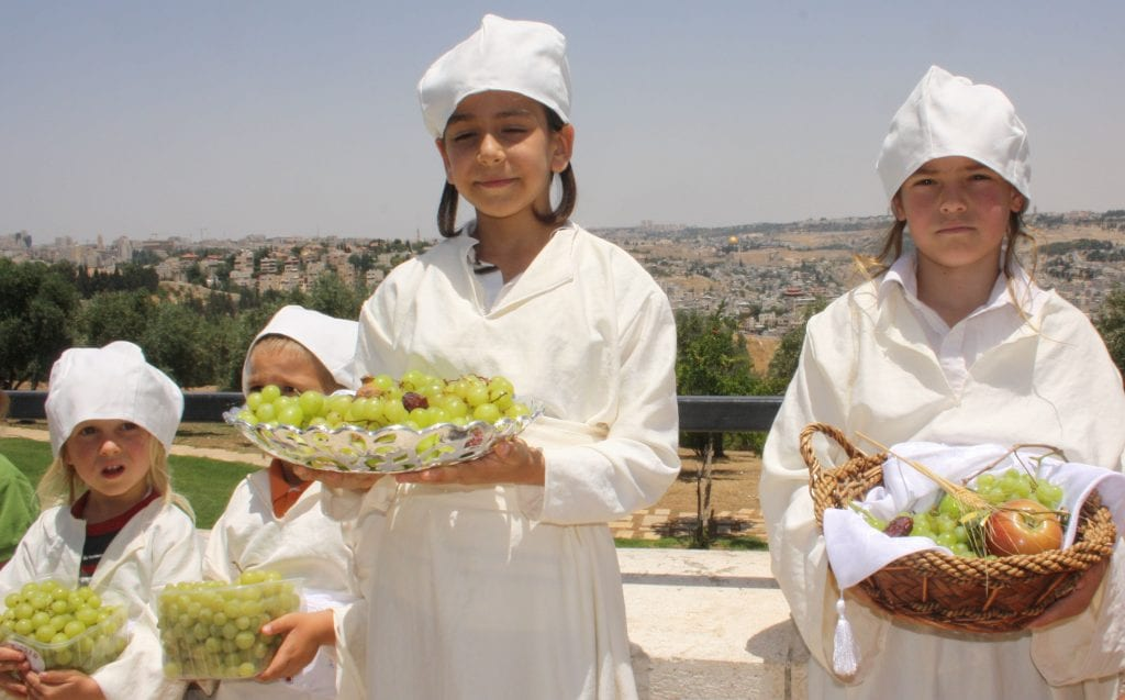 Children adorn the traditional white garments of the Kohein (priests) as they reenact the offering of the first fruits. (Photo: Adam Propp)