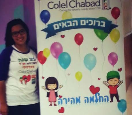 A volunteer stands next to the banner celebrating 35 years of Colel Chabad's work at the hospital. (Photo: Colel Chabad)