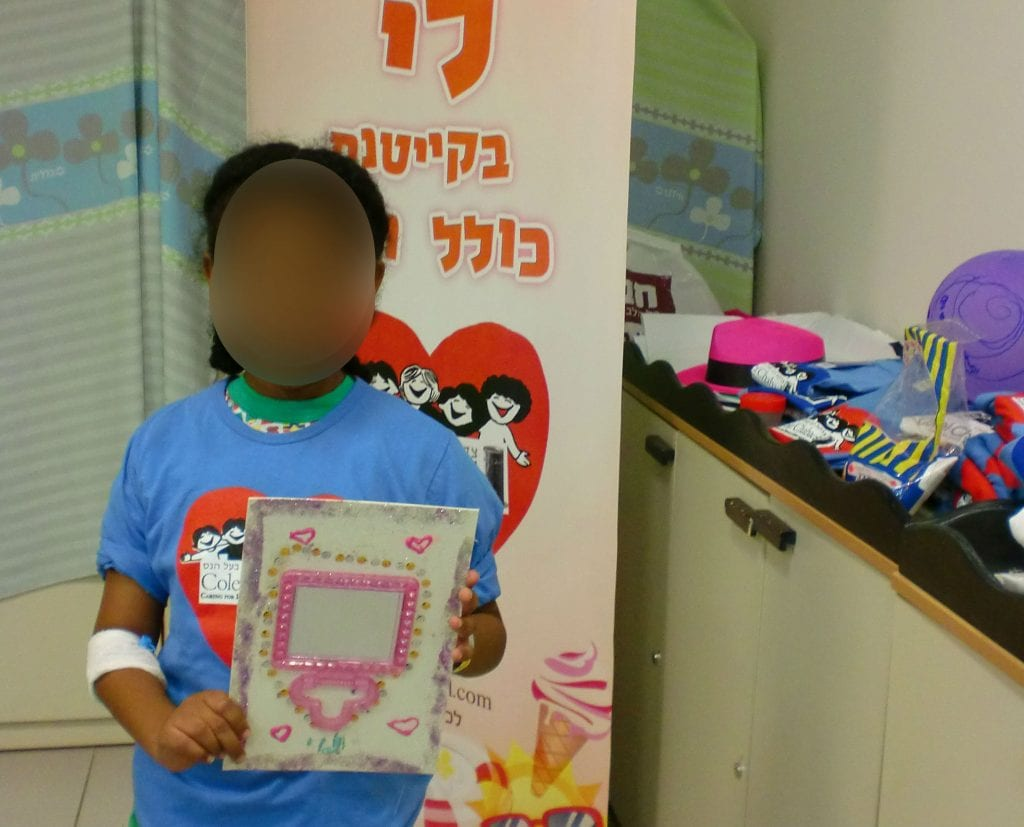 A child shows off a toy she received from Colel Chabad. (Photo: Colel Chabad)