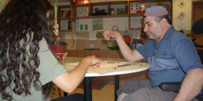 A patient at Colel Chabad's Grabski Center in Migdal HaEmek sits with his caregiver. (Photo: Colel Chabad)